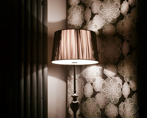 Lamp creating beautiful shadows complementing the wallpaper