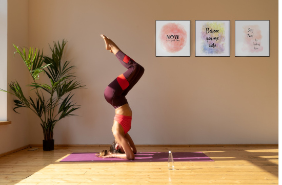 Colourful motivational art in warm and cosy yoga studio - woman doing elbow stand yoga pose.