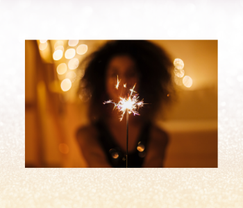 A golden light photo of a woman holding sparkle