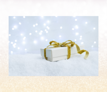 A white gift box with gold ribbon surrounded by bright lights