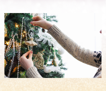 Woman decorating a christmas tree with white, gold and silver decorations