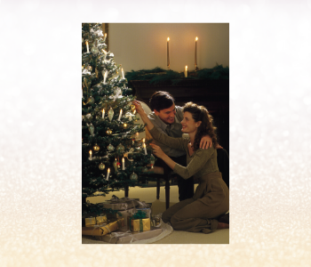 Man and woman decorating a Christmas tree with white, gold and silver decorations