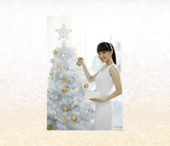 A woman decorating a white and gold Christmas tree