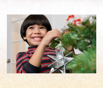 Kid smiling while decorating a tree